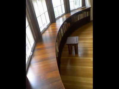 Custom built curved Ipe and Walnut bookcase to match curve of house