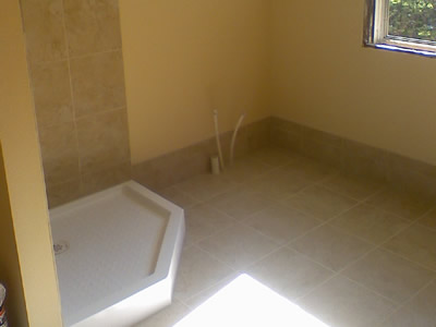 Tile floor, baseboard, and shower stall